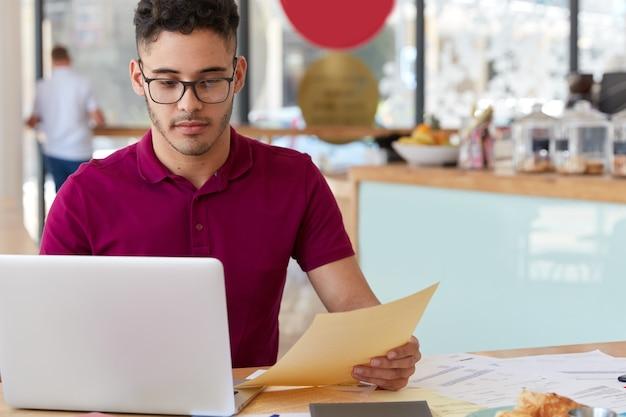カジュアルな服装で自信を持っている男性は、電子決済を提供し、ラップトップコンピューターでオンラインバンキングアプリケーションを使用し、webサイトのページを開発し、書類を保持し、居心地の良いコーヒーショップで働いています。現代のテクノロジー