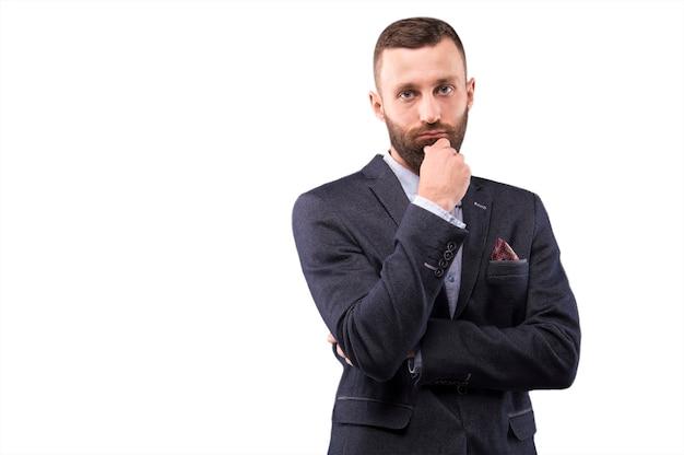 Уверенный в себе мужчина приложил руку к бороде и посмотрел в камеру