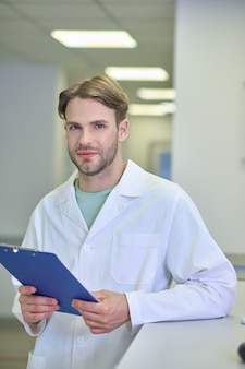 Confident man in medical gown with folder