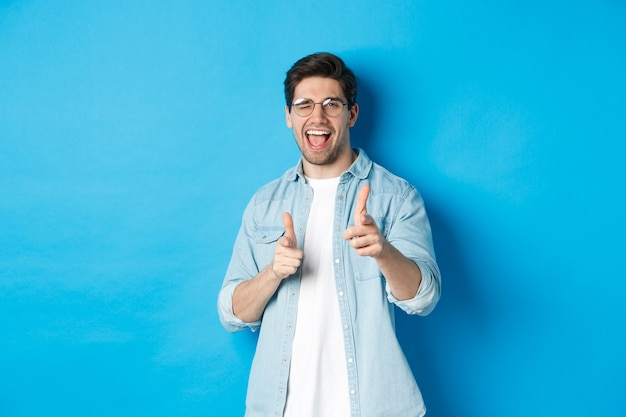 Uomo fiducioso che dice congratulazioni, strizza l'occhio e indica te, in piedi contento su sfondo blu e sorridente