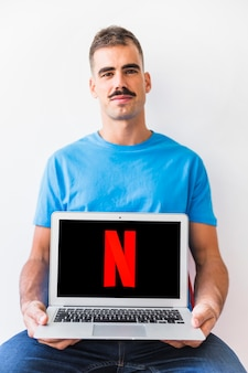 Confident man showing Netflix logo