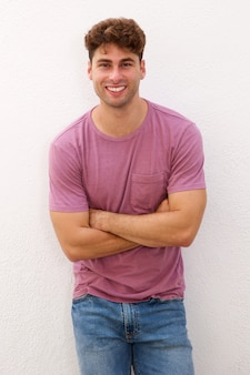 Confident man standing with arms crossed by white wall