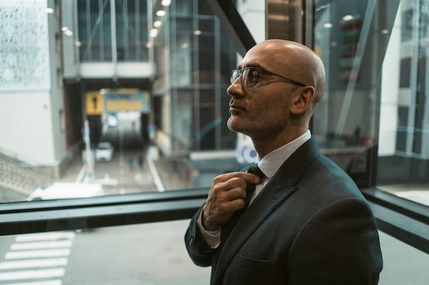 Уверенный мужчина поправляет галстук перед хорошей сделкой. кавказский бизнесмен в бизнес-центре