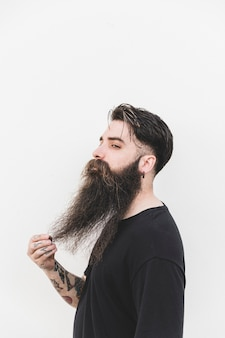 Confident man touching his beard standing against white backdrop