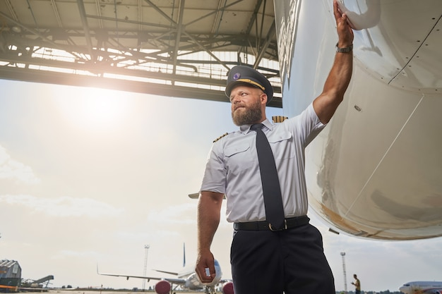 Confident man in the uniform putting his hand on the fuselage and looking into the distance