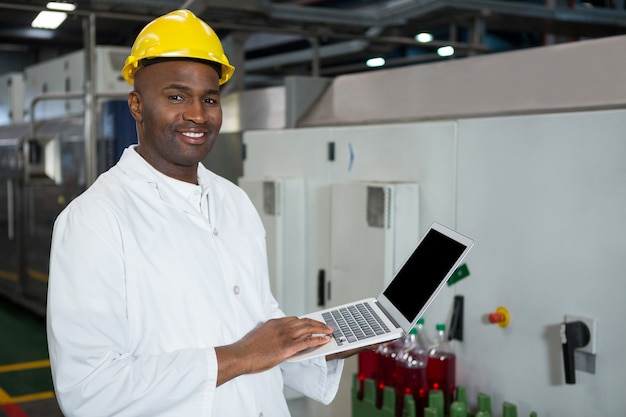 Confident man using laptop in juice factory