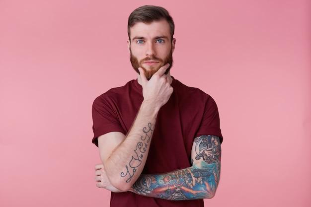 Un uomo fiducioso con la barba e con la mano tatuata, tiene la mano sul mento, pensa a qualcosa, costruisce un piano, medita una bella idea. isolato su sfondo oink.
