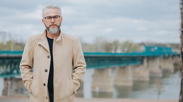 後ろに橋のあるスタイリッシュな茶色のコートを着た白髪の自信のある男
