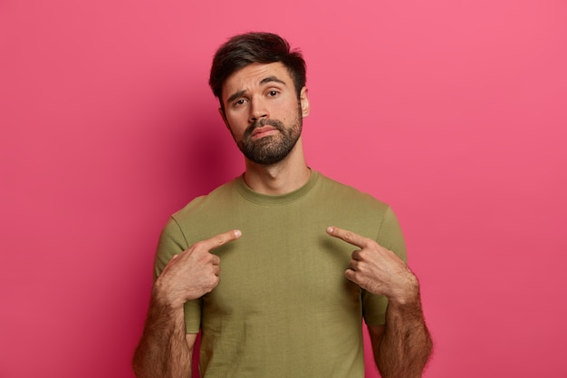 Uomo fiducioso con una folta barba, indica se stesso