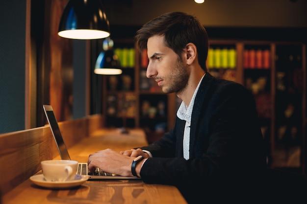 Уверенный в себе человек работает на ноутбуке, имея кофе