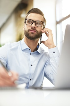 전화로 협상에 참여하는 자신감 있는 관리자