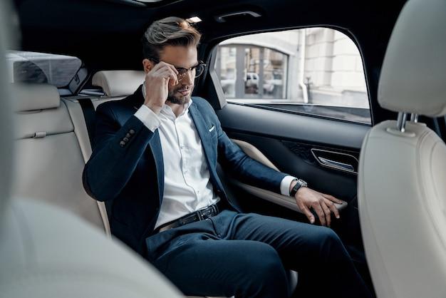 자신감 있는 매니저. 차에 앉아있는 동안 그의 안경을 조정 전체 정장에 잘 생긴 젊은 남자