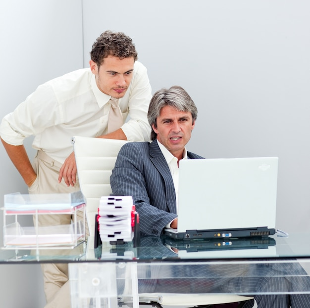 Confident manager helping his colleague work at a computer