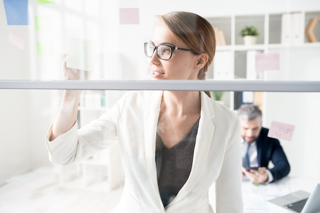 Confident marketing expert making notes on glassy board