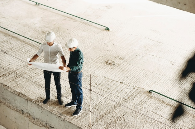 자신감있는 마스터는 흰색 셔츠를 입고 건물의 평면도를보고 건축중인 건물 내부 작업에 대해 건축가와 이야기합니다.