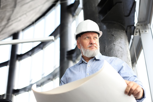 Confident mature architect in corporate suit and hardhat holding a blueprint and looking at it.