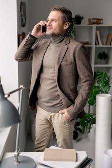 同僚やクライアントと相談しながら、オフィスの窓際にスマートフォンが立っている自信のある成熟した建築家