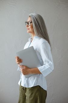 Confident mature asian business lady in blouse holds laptop in studio side view