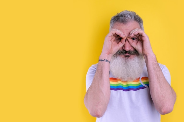 Confident mature bearded man dressed with lgbtq symbols t-shirt looking at camera, studio portrait of homosexual man, yellow background