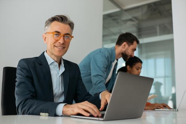 オフィスで働くラップトップ コンピューターを使用して自信を持って成熟したビジネスマン