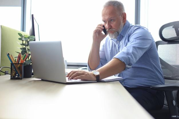 현대 사무실에서 스마트폰으로 전화를 걸고 있는 자신감 있는 성숙한 사업가.