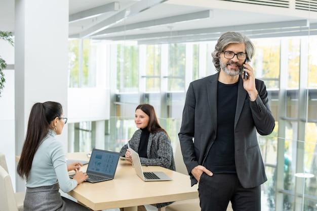 Уверенный зрелый бизнесмен в формальной одежде разговаривает с клиентом по мобильному телефону против двух коллег-женщин, работающих над проектом за столом