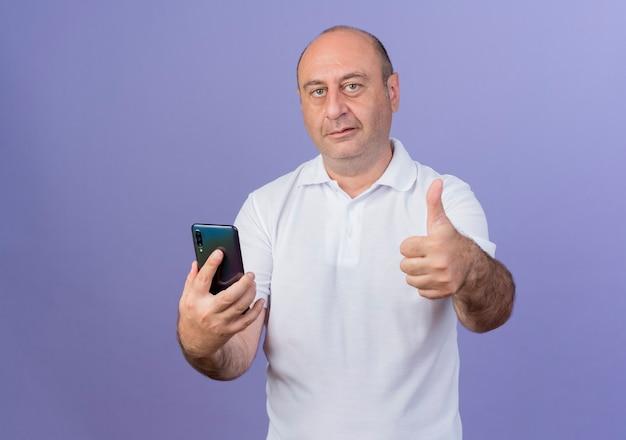 Уверенный в себе зрелый бизнесмен, смотрящий на фронт, держащий мобильный телефон и показывающий большой палец вверх
