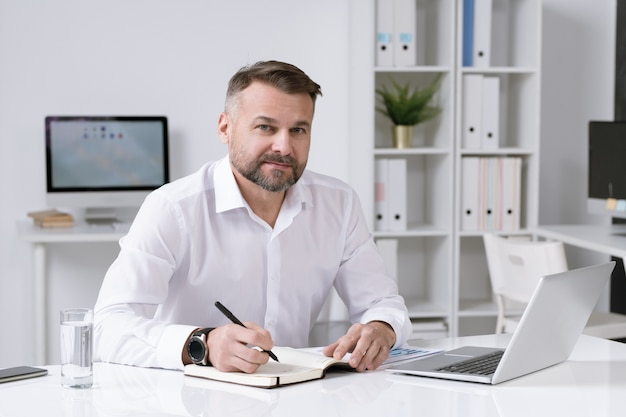 Уверенно зрелый бизнесмен сидит за столом в своем офисе, записывая рабочий план в блокноте
