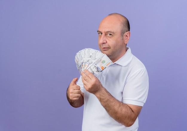 Уверенный в себе зрелый бизнесмен, стоящий в профиле, держит деньги и показывает палец вверх