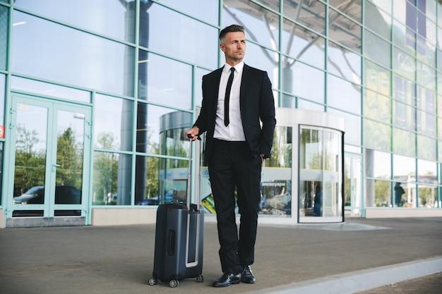 空港の外に立っている自信を持って成熟した実業家