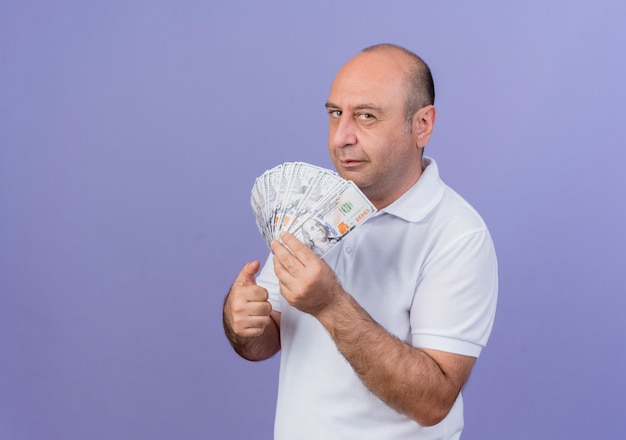 Confident mature businessman standing in profile view holding money and showing thumb up