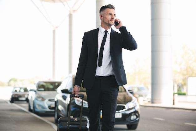 Уверенно зрелый бизнесмен разговаривает по мобильному телефону