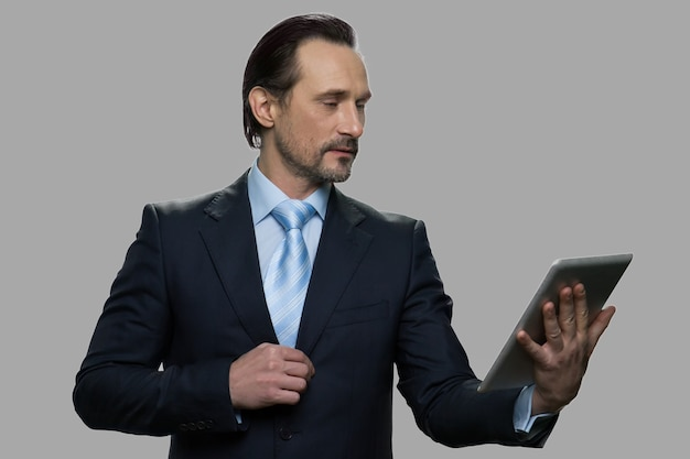 Confident mature businessman using digital tablet. successful caucasian executive having video chat against gray background. people, business, online communication concept.