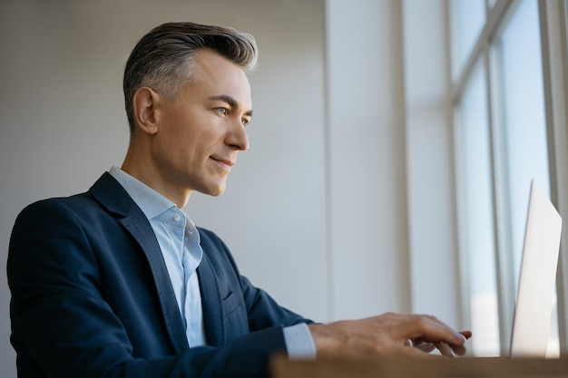 Confident mature businessman using laptop computer