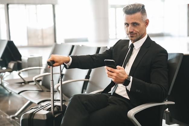 携帯電話を使用して自信を持って成熟した実業家