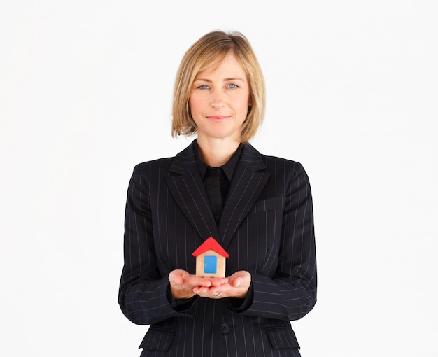 Confident mature businesswoman holding a house