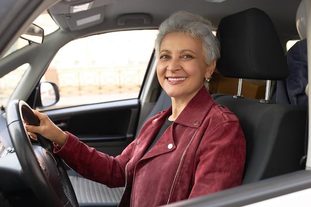 Уверенная зрелая бизнес-леди в стильной куртке за рулем автомобиля по улицам города