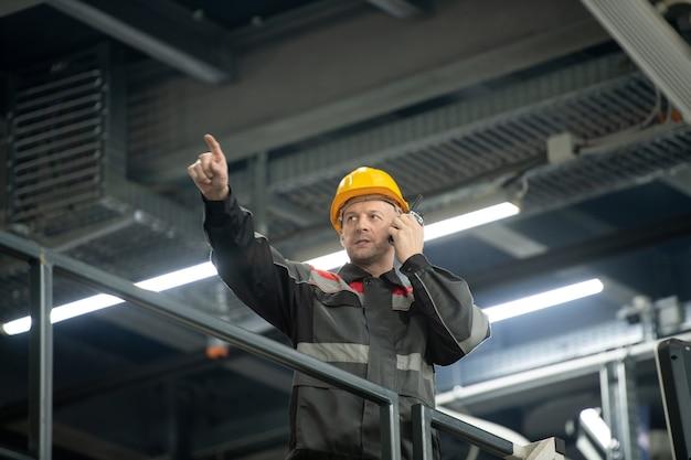 대형 폴리머 가공 공장에서 일하는 동안 머리에 안전모를 쓰고 귀로 앞을 가리키는 워키토키를 쓴 자신감 있는 성숙한 감독