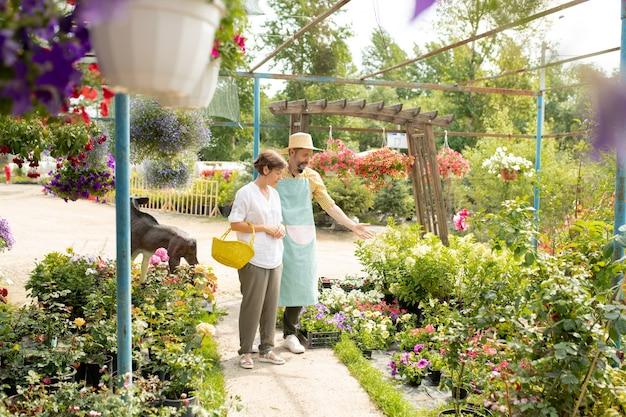 帽子とエプロンで自信を持って成熟した庭師が彼のガーデンセンターでクライアントの1人に白い花を見せています