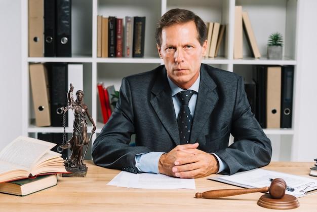Уверенный зрелый адвокат, сидящий в зале суда