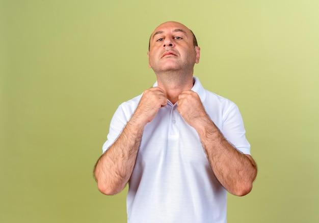 올리브 녹색 벽에 고립 된 칼라를 들고 확신 성숙한 남자