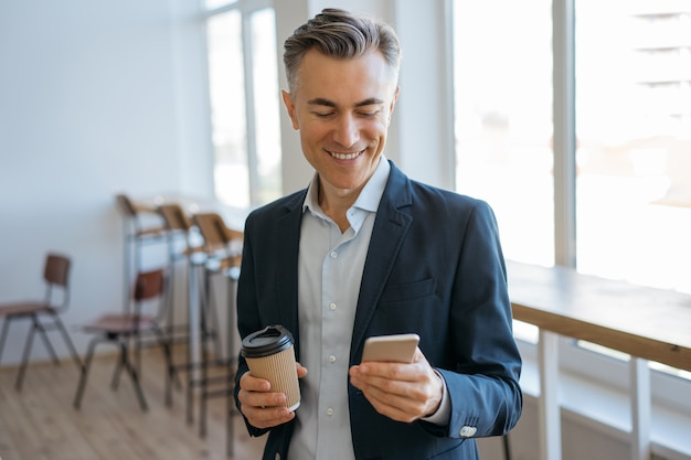 Confident mature man holding smartphone and cup of coffee, reading news, communication online in office