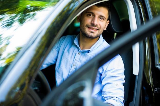 Уверенный зрелый мужчина в строгой одежде открывает дверь машины