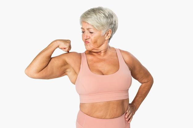 Уверенная зрелая женщина в спортивной одежде, позирующая ее мышцы