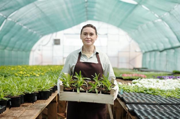 큰 온실의 통로에 서 있는 작업복에 자신감이 성숙한 여자