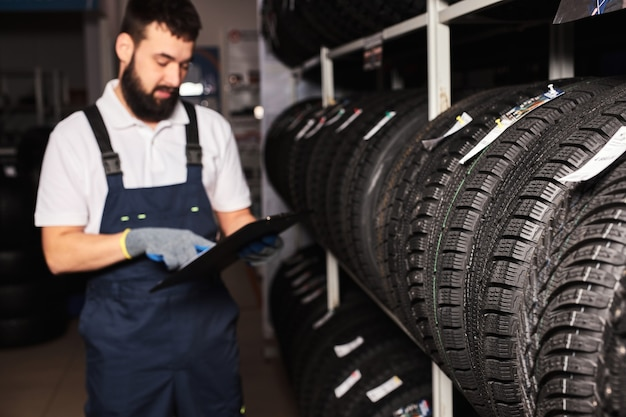 Confident meachanic man during work, focus on tires at the repair garage. replacement of winter and summer tires. seasonal tire replacement concept.
