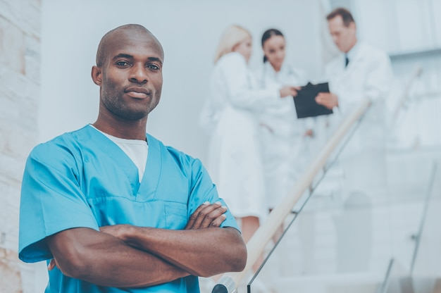 Confident medical expert. confident african doctor in blue uniform keeping arms crossed and looking at camera while his colleagues talking in the background