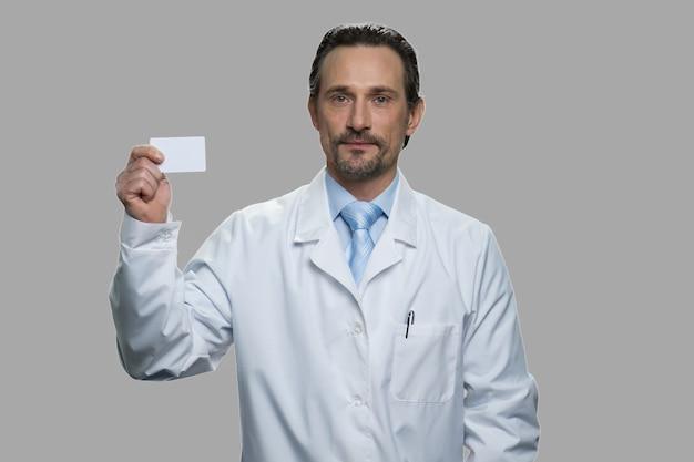 빈 명함을 들고 자신감 의료 노동자입니다. 회색 배경에 명함을 보여주는 흰색 코트에 성숙한 남자.