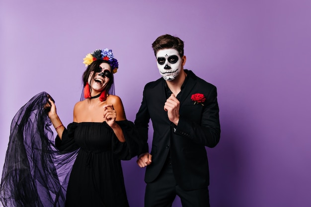 Confident mexican guy dancing with girlfriend in day of the dead. married couple celebrating halloween in masquerade costumes.