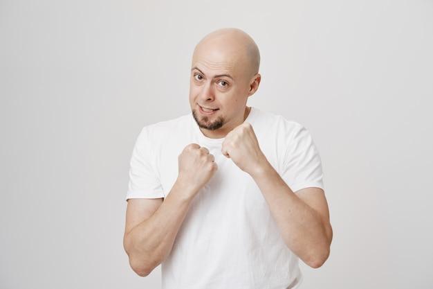 Уверенный в себе лысый парень средних лет готов драться, сжимая кулаки